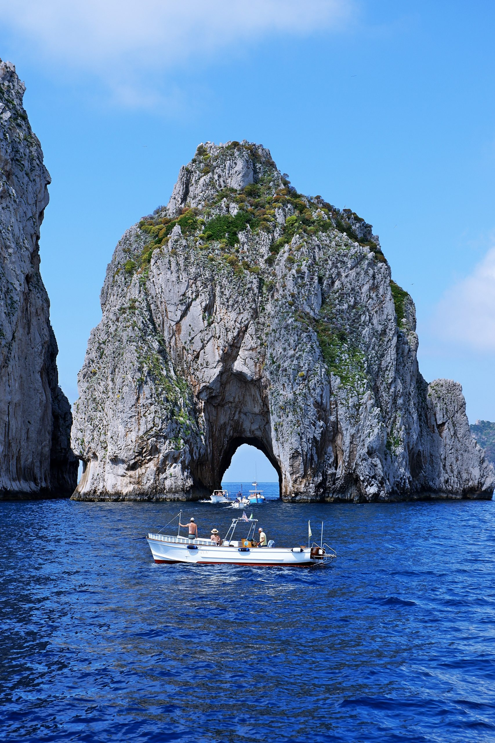 white power boat beside rock formation