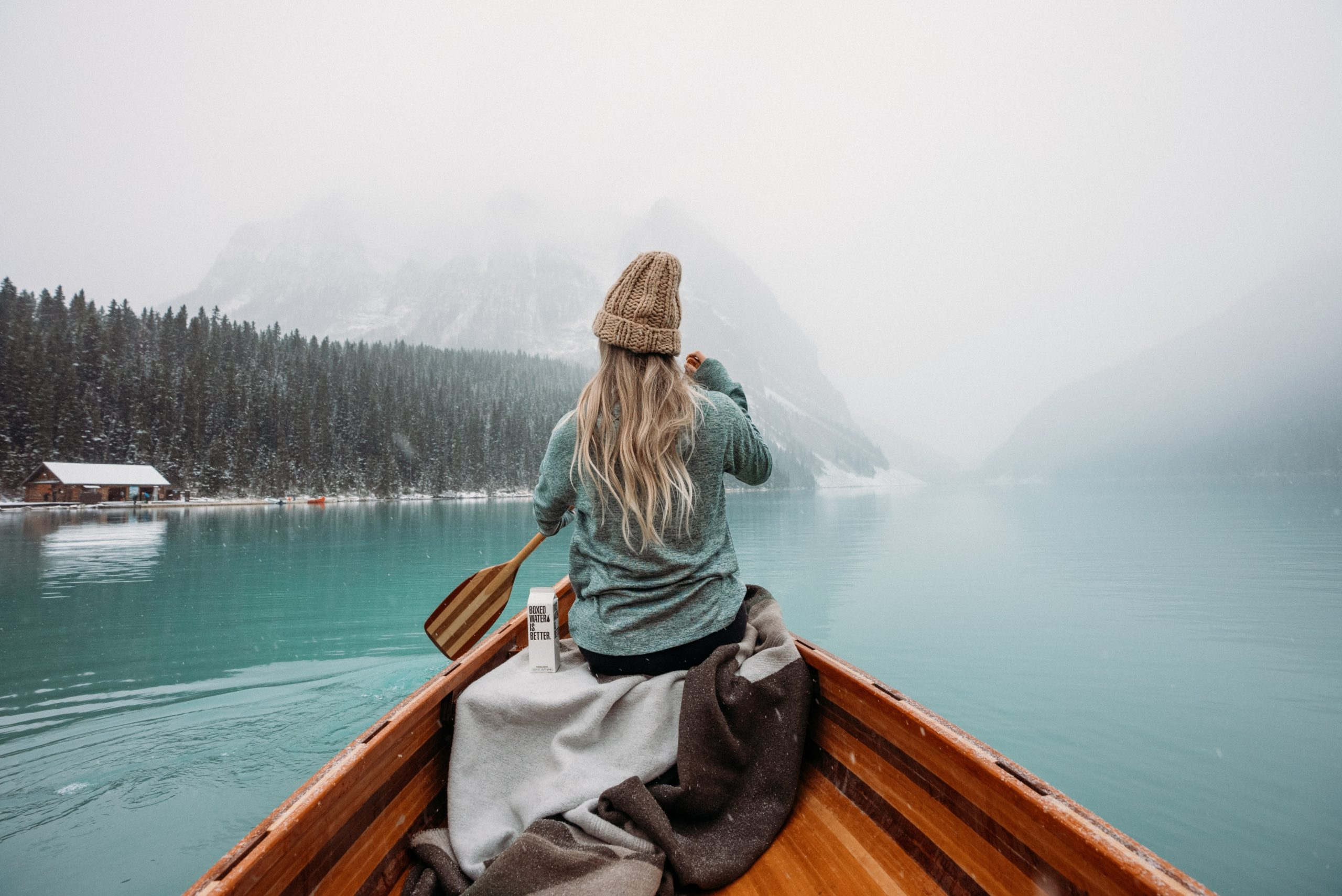 woman in gray hoodie sitting on brown wooden boat on lake during daytime